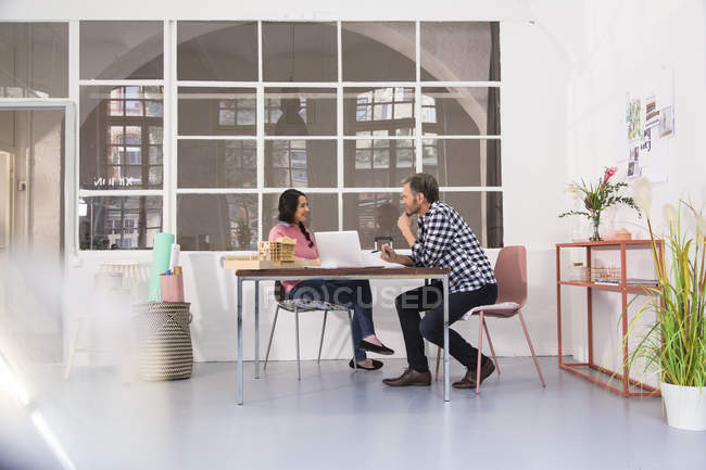Smiling colleagues sitting at table in an architect's loft office — Stock Photo