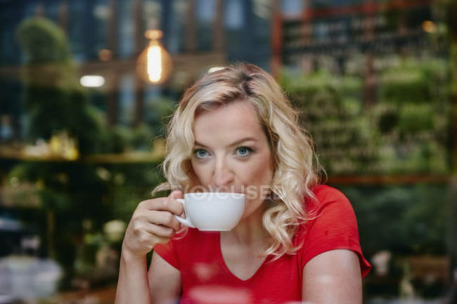 Portrait of blond woman drinking coffee in a cafe — Stock Photo