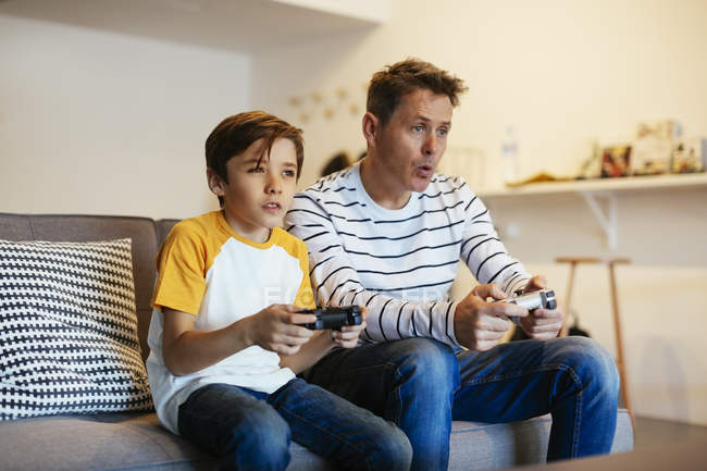 Father and son playing video game on couch at home — Stock Photo