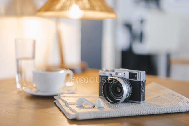 Auricolare, giornale e macchina fotografica sul tavolo in un caffè — Foto stock