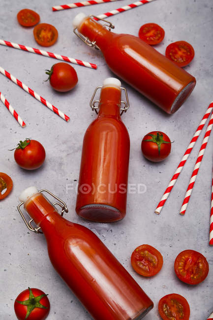 Homemade tomato juice in swing top bottles, straws and tomatoes on grey ground — Stock Photo