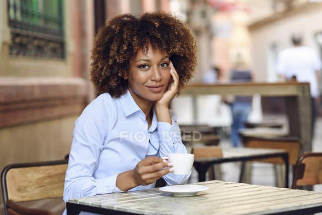 Портрет усміхнена жінка з афро зачіска сидить у відкритому кафе — стокове фото