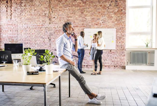 Бизнесмен по мобильному телефону в офисе с коллегами в фоновом режиме — стоковое фото
