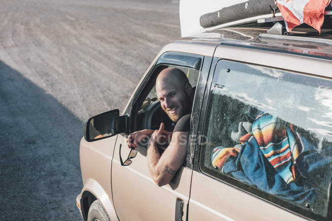 Portrait of happy young man with minivan on a road trip — Stock Photo