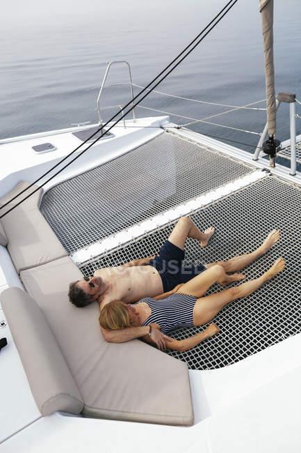 Літня пара на вітрильній поїздки лежачи на батуті, розслабляючий — стокове фото
