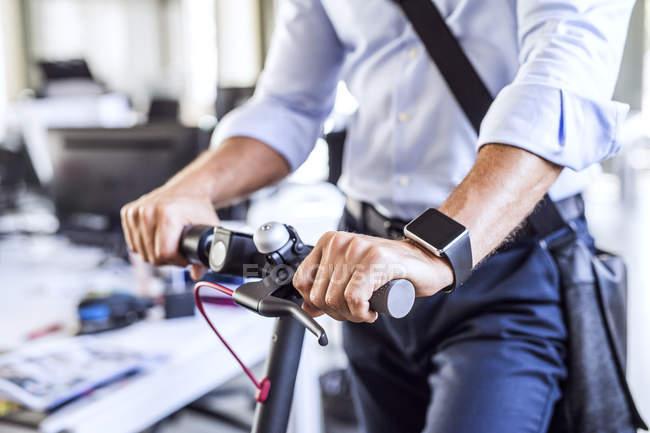 Gros plan de l'homme d'affaires moderne avec scooter dans le bureau — Photo de stock