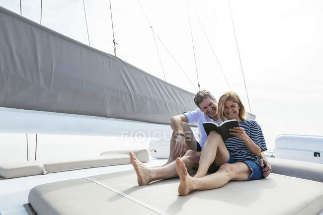 Pareja sentada en cubierta de catamarán, relajante, mujer leyendo libro - foto de stock