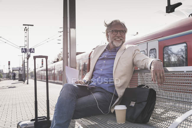 Smiling mature businessman sitting at train station with cell phone, earbuds and notebook — Stock Photo