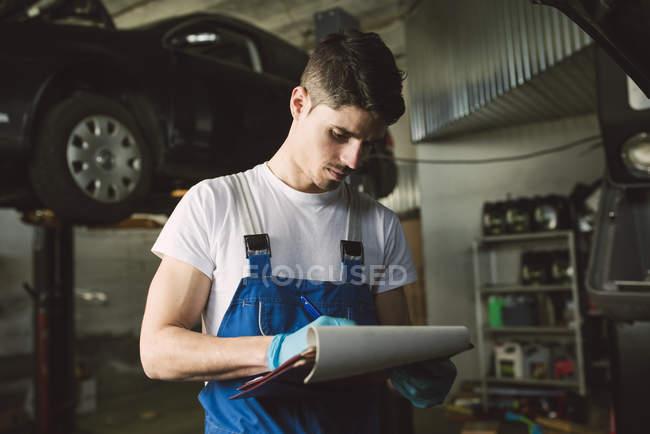 Mecánico con portapeles y listas de verificación en su taller. - foto de stock