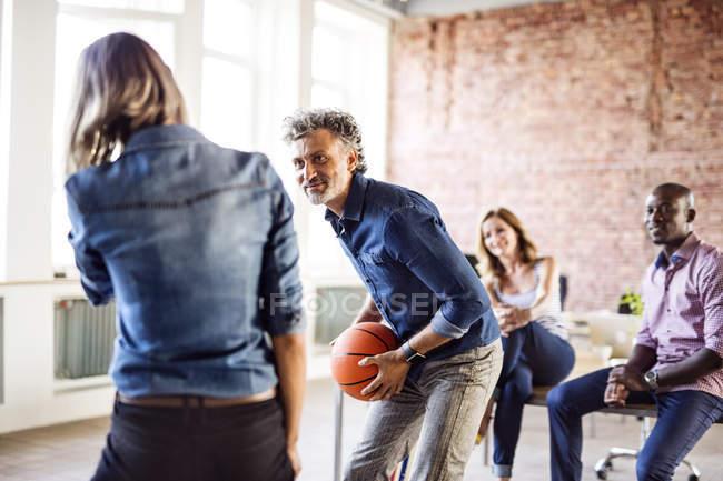 Коллеги, играющие в баскетбол в офисе — стоковое фото