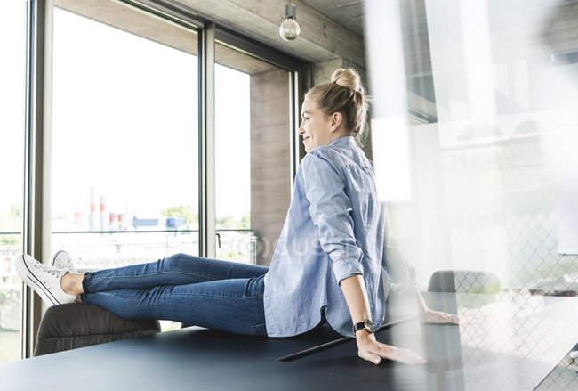 Молодая деловая женщина сидит на столе — стоковое фото