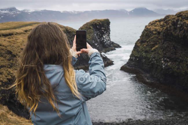 Islandia, vista trasera de una mujer joven tomando fotos con teléfono inteligente en la costa - foto de stock