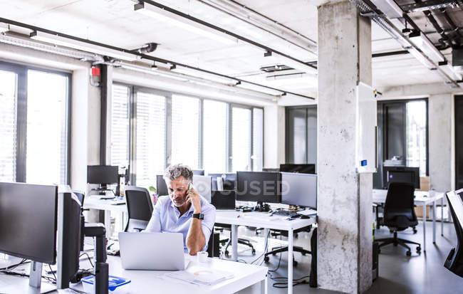 Зрелый бизнесмен сидит за столом в офисе и пользуется мобильным телефоном и ноутбуком — стоковое фото