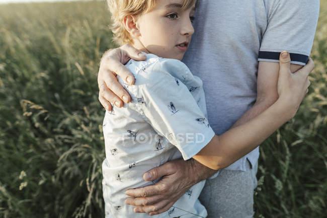 Мальчик обнимает отца на лугу — стоковое фото