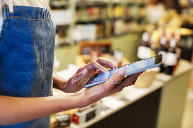 Крупный план женщины, использующей планшет в магазине — стоковое фото