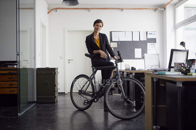 Businesswoman with bicycle in her start-up company — Stock Photo