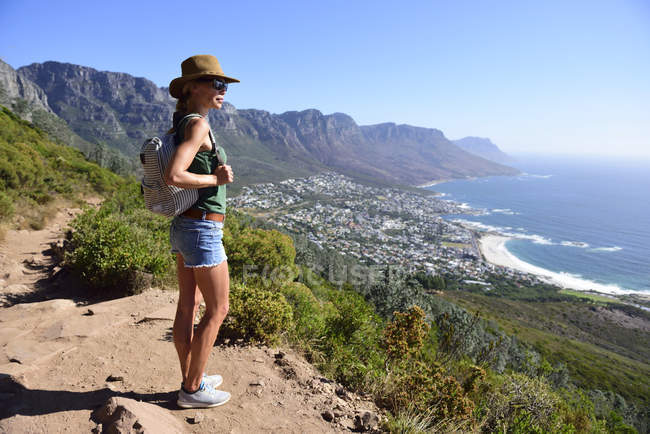 South Africa, Cape Town, woman standing looking at the coast during hiking trip to Lion 's Head — стоковое фото