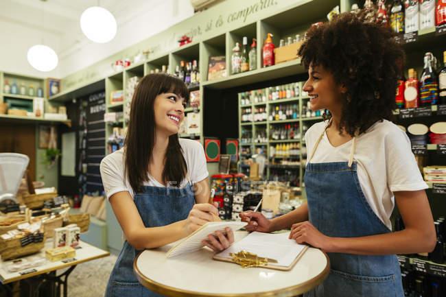 Deux femmes souriantes debout dans un magasin prenant des notes — Photo de stock