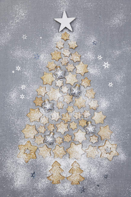Star-shaped biscuits and Christmas baubles forming Christmas Tree on grey background — Stock Photo