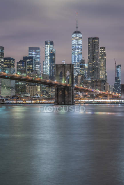 Usa, Nueva York, Manhattan, Brooklyn, paisaje urbano con Brooklyn Bridge por la noche - foto de stock