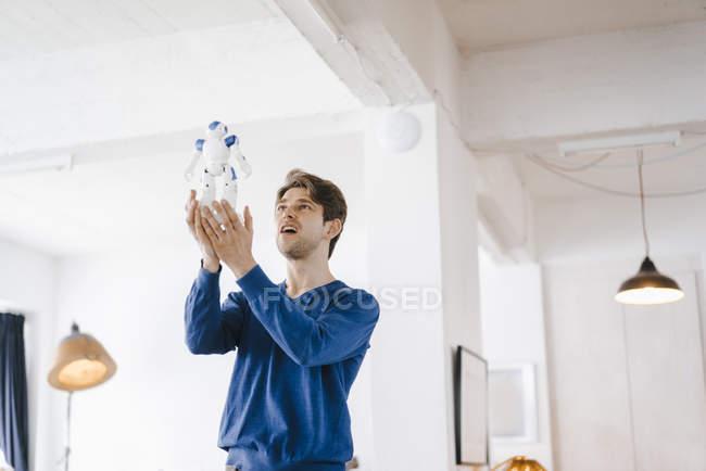 Homme tenant un robot dans les mains — Photo de stock