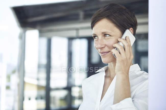 Портрет улыбающейся деловой женщины по мобильному телефону — стоковое фото