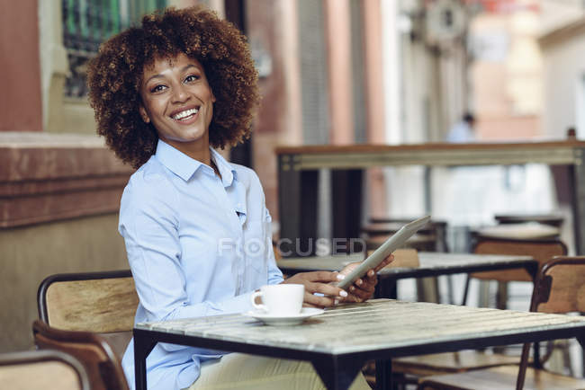 Lächelnde Frau mit Afro-Frisur sitzt mit Tablet im Café — Stockfoto