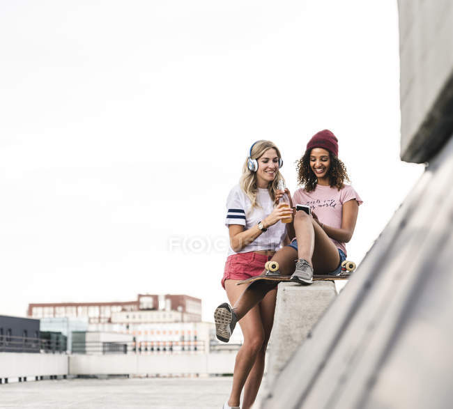 Best friends with skateboard, having fun together, listening music — Stock Photo