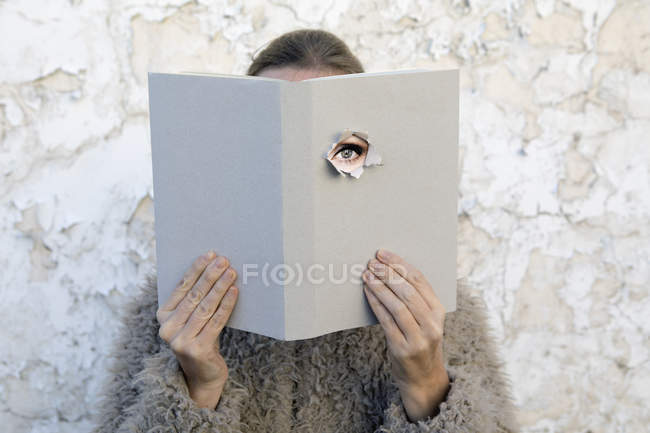 Woman covering face with book, reading poetry, eye looking through cover — Stock Photo