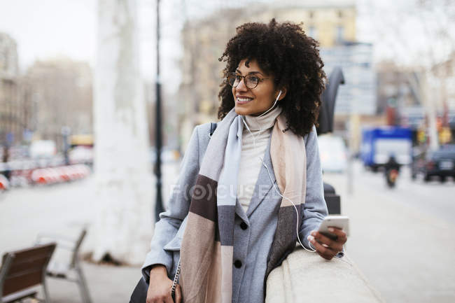 Spain, Barcelona, smiling woman with cell phone and earphones walking in city — Stock Photo