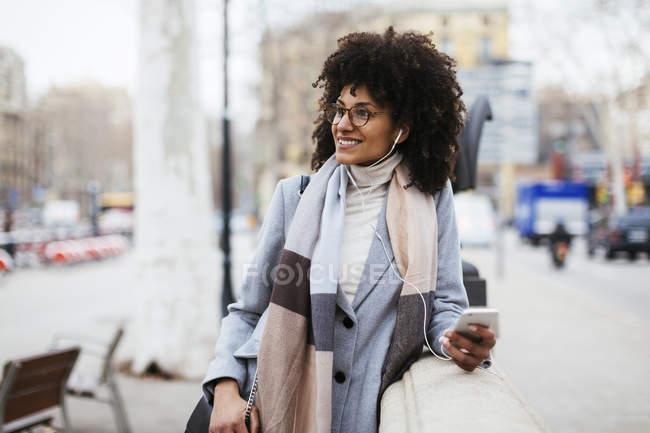 Іспанія, Барселона, усміхнена жінка з мобільного телефону і навушники ходьба в місті — стокове фото