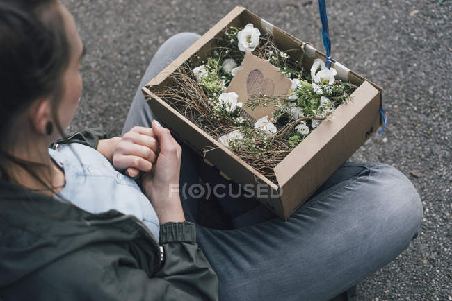 Donna con disposizione floreale in scatola di cartone seduta a terra — Foto stock