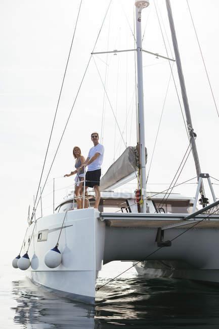Mature couple making holidays, sailing on a catamaran — Stock Photo