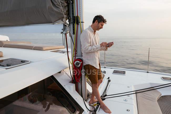 Marure man en catamaran, avec smartphone — Photo de stock