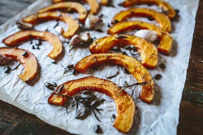 Fette al forno di zucca, aglio e rosmarino su carta da forno — Foto stock