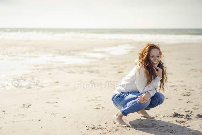 Mulher ruiva relaxando na praia, agachado — Fotografia de Stock