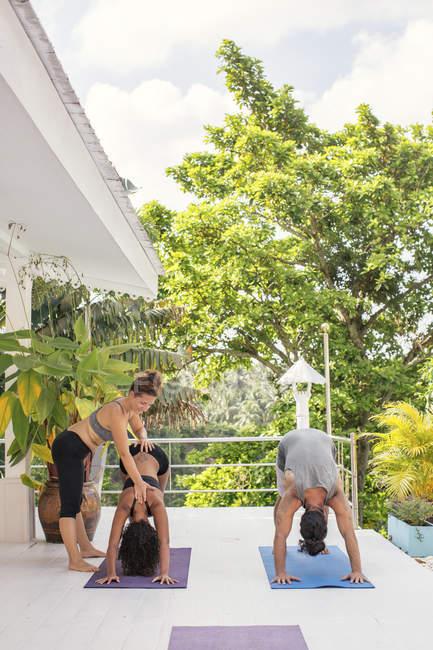 Инструктор по йоге учит женщину правильно позировать йогой на террасе — стоковое фото
