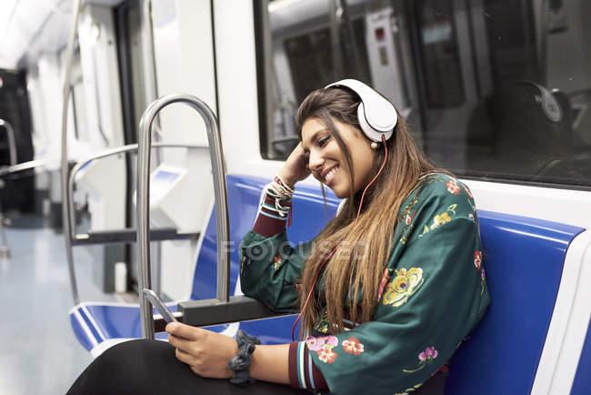 Sorrindo jovem ouvindo música com fones de ouvido e smartphone no trem subterrâneo — Fotografia de Stock