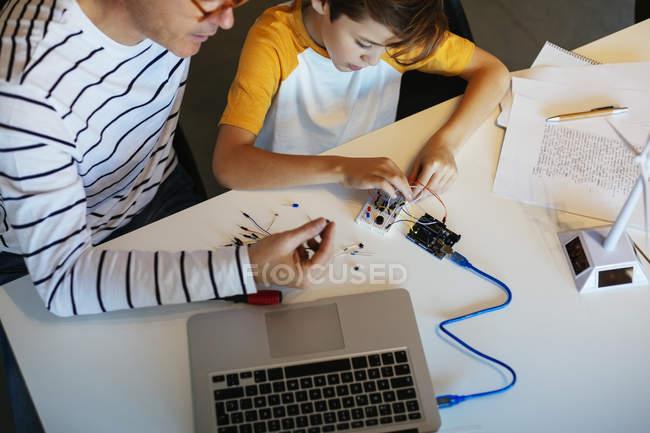 Pai e filho montando um kit de construção com modelo de turbina eólica — Fotografia de Stock