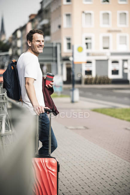 Smiling man with rolling suitcase and takeaway coffee in the city — Stock Photo