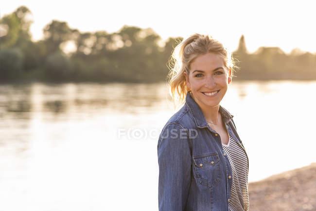 Portrait de femme blonde au bord de la rivière le soir — Photo de stock