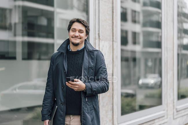 Retrato de un joven sonriente con teléfono celular en la ciudad - foto de stock