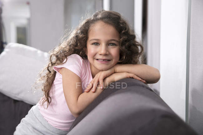 Porträt eines lächelnden kleinen Mädchens mit Zahnlücke auf der Couch — Stockfoto
