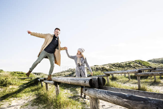 Жінка допомагає людині балансування на дерев'яні ставки в дюнах — стокове фото