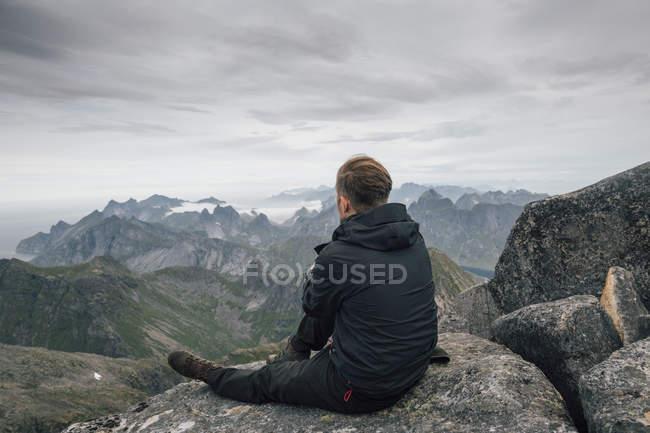 Noruega, Lofoten, Moskenesoy, Jovem sentado em Hermannsdalstinden, olhando sobre Kjerkefjord — Fotografia de Stock