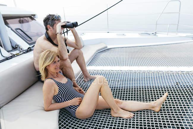 Mature couple sitting on catamaran trampoline, using binoculars — Stock Photo