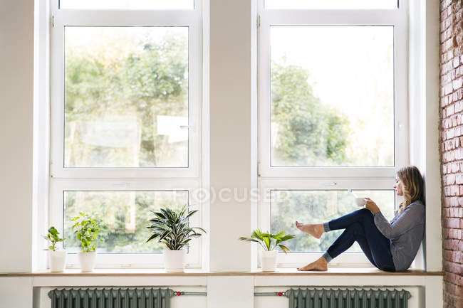 Woman sitting at home on the window sill, drinking coffee — Stockfoto