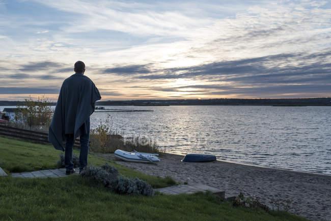 Человек, стоящий на берегу озера на закате — стоковое фото