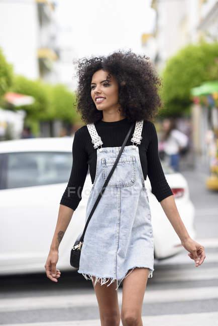 Sorridente giovane donna che attraversa la strada — Foto stock