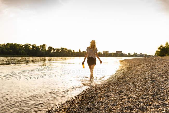 Giovane donna che cammina a piedi nudi sul fiume la sera — Foto stock